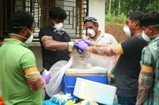 Animal Husbandry department and Forest officials deposit a bat into a container after catching it inside a well at Changaroth in Kozhikode in the Indian state of Kerala on May 21